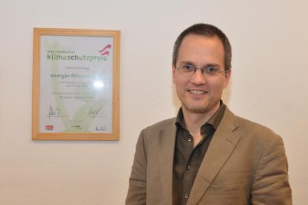 Mag. (FH) DI Markus Piringer vor der Urkunde des österreichischen Klimaschutzpreises